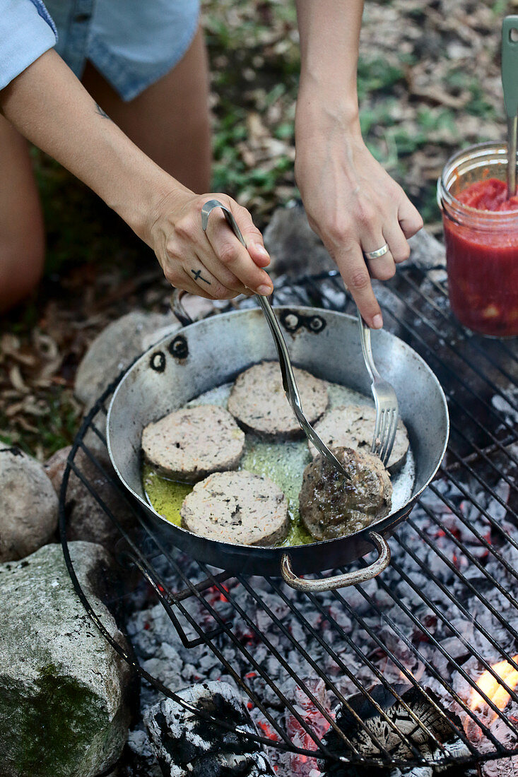Slices of meat loaf being fried in a pan over a campfire