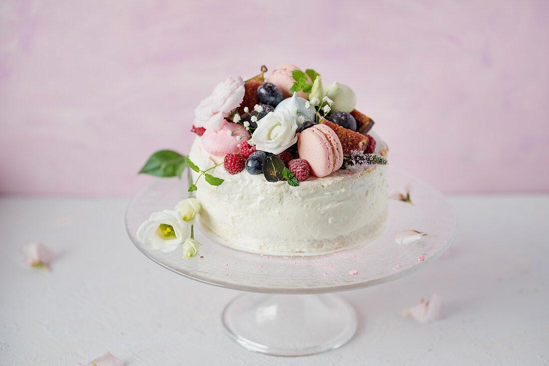 Festliche Torte mit Macarons und Beeren verziert