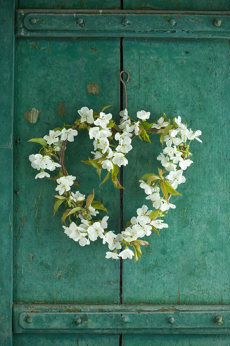 Cherry-blossom heart-shaped wreath on rustic cupboard door