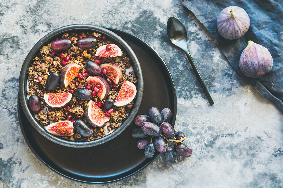 Yoghurt with muesli, figs, grapes and pomegranate seeds