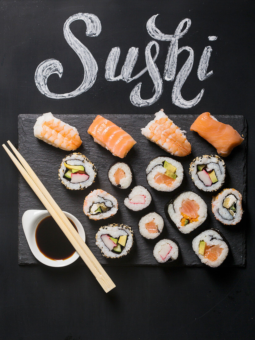 Sushi served on blackboard with the word Sushi handwritten with chalk