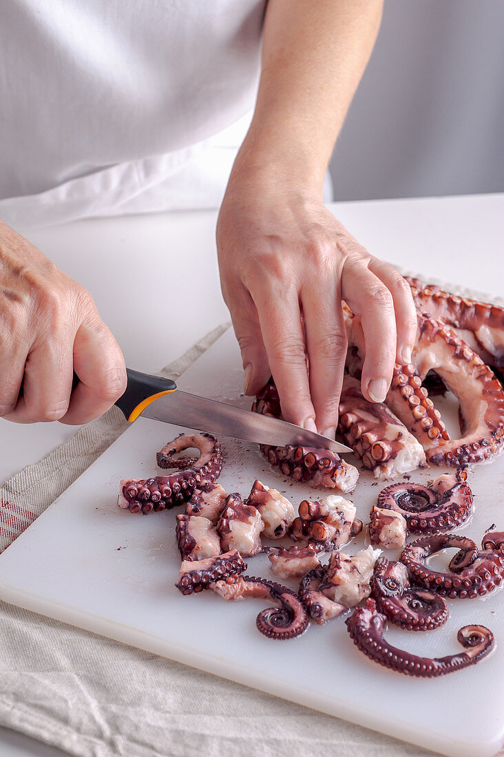Gently cooked octopus being chopped