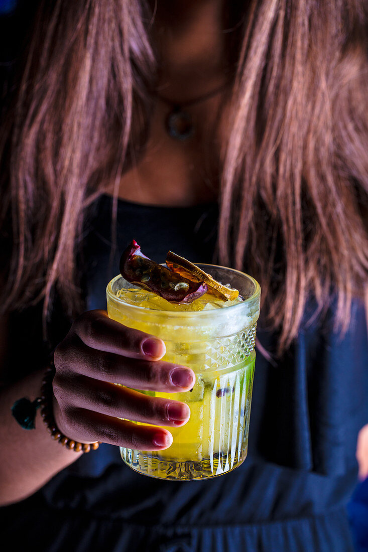 A woman holding a passion fruit cocktail in a glass