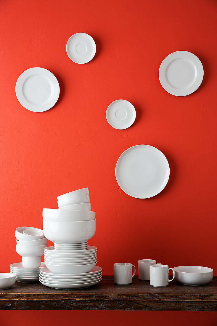 White crockery on table and white plates on red wall
