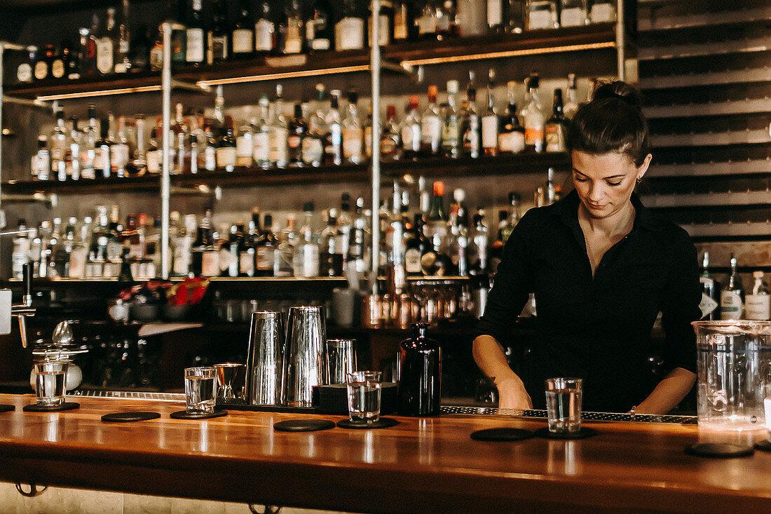 A bar tender working behind a bar (Suderman Bar, Cologne, Germany)