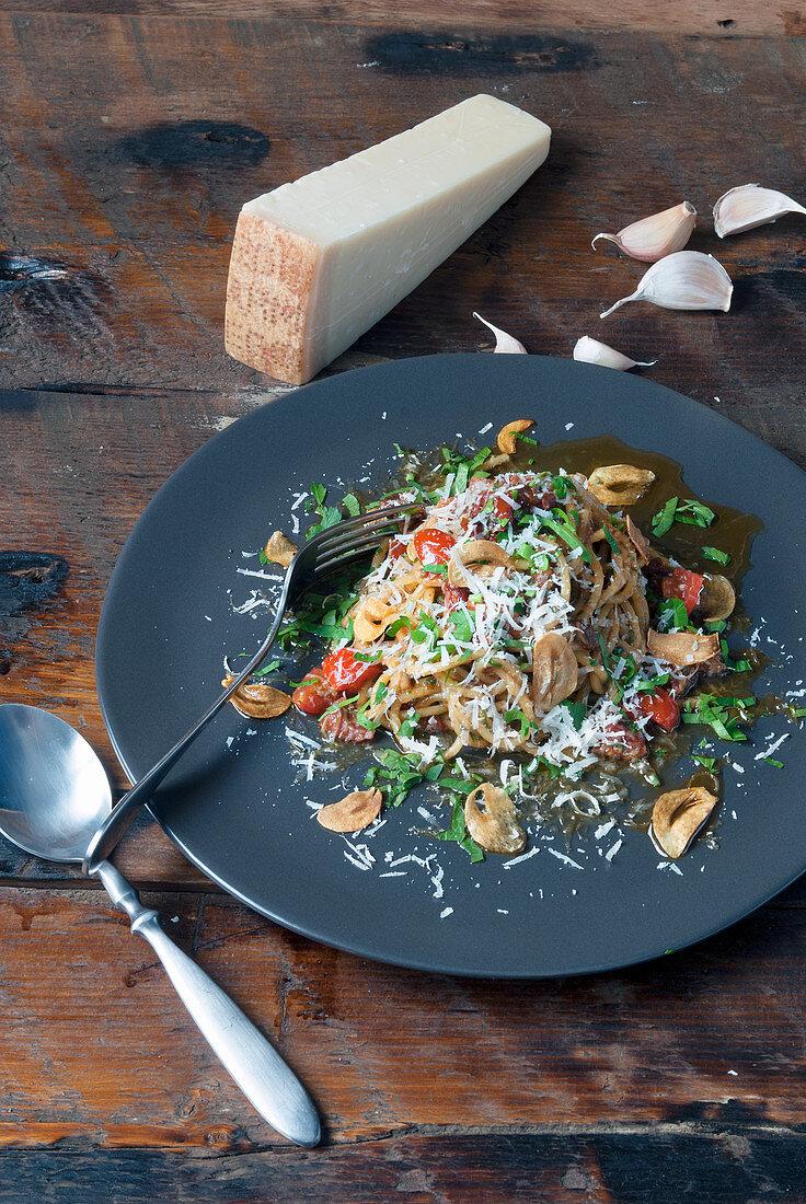 Pasta dish with mushrooms tomatoes and Parmesan cheese