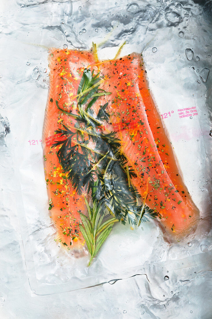 Vacuum packed char fillets with herbs in water