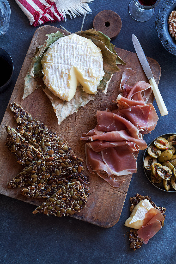An appetizer platter with soft cheese, ham, olives and crackers (keto cuisine)
