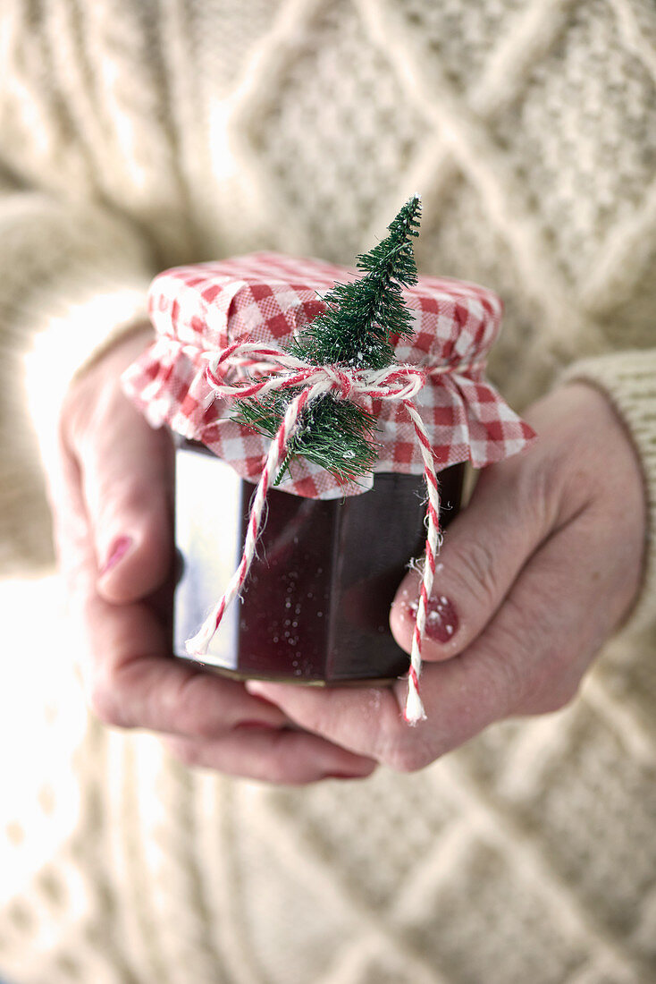 A hand holding a jar of jam with Christmas decorations