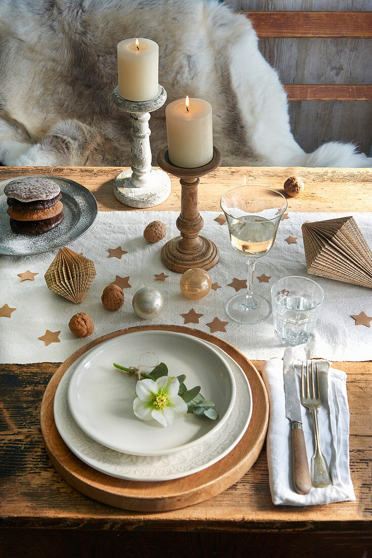A place setting with a Christmas rose on a table decorated for Christmas