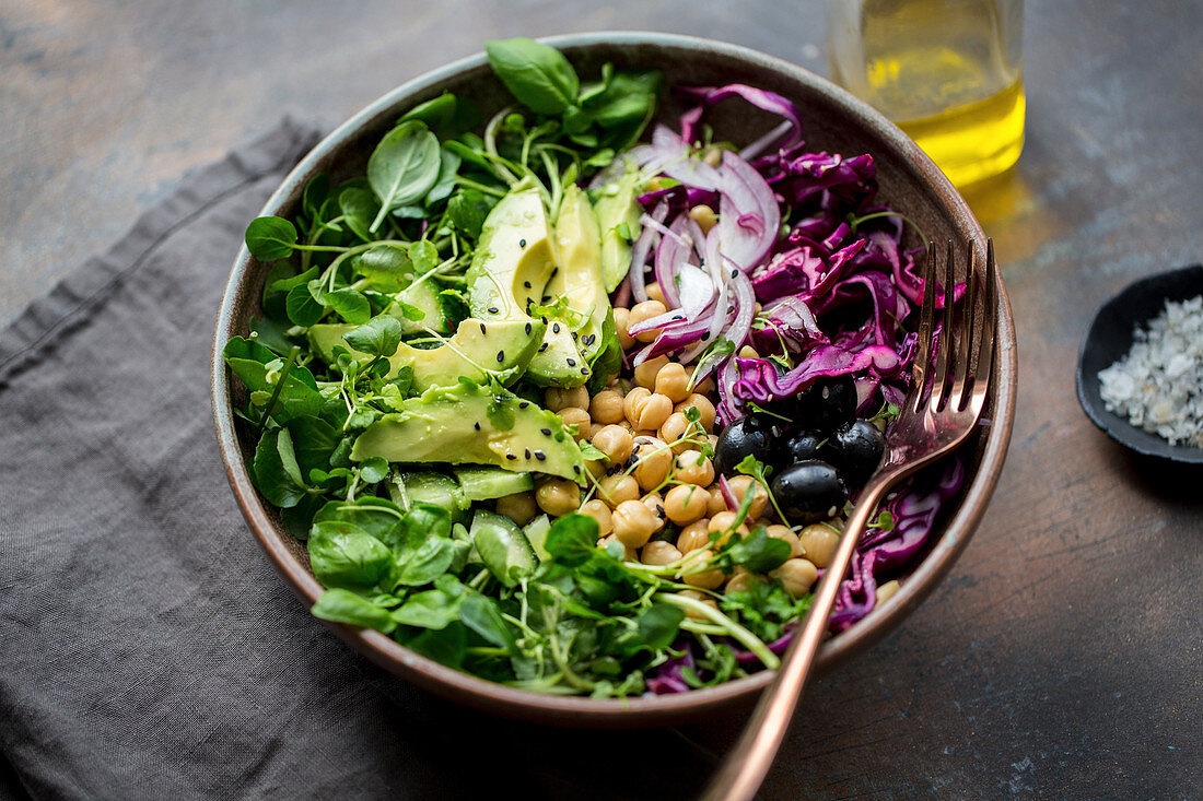 A salad bowl with avocado, chick peas, red cabbage and water cress