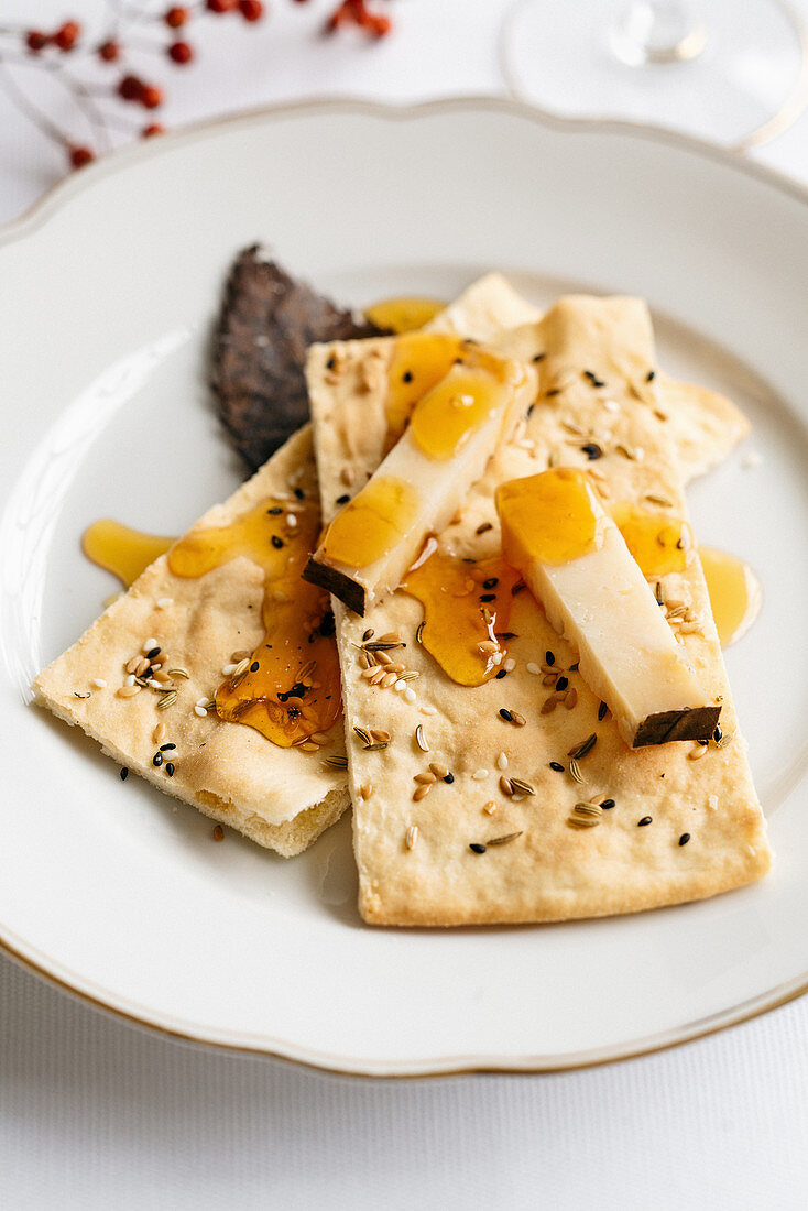Homemade sesame seed crackers with Occelli cheese and chestnut honey