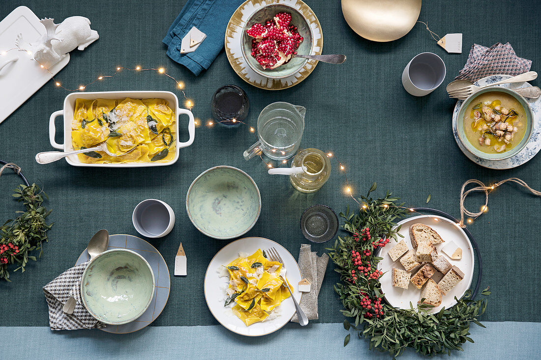 Christmas dinner on a grey table with a chain of fairy lights and a Christmas wreath