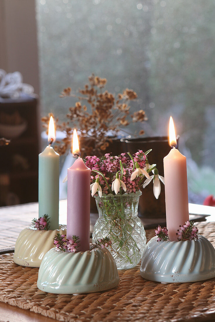 Burning candles in Bundt cake candle holders with snowdrops as table decoration