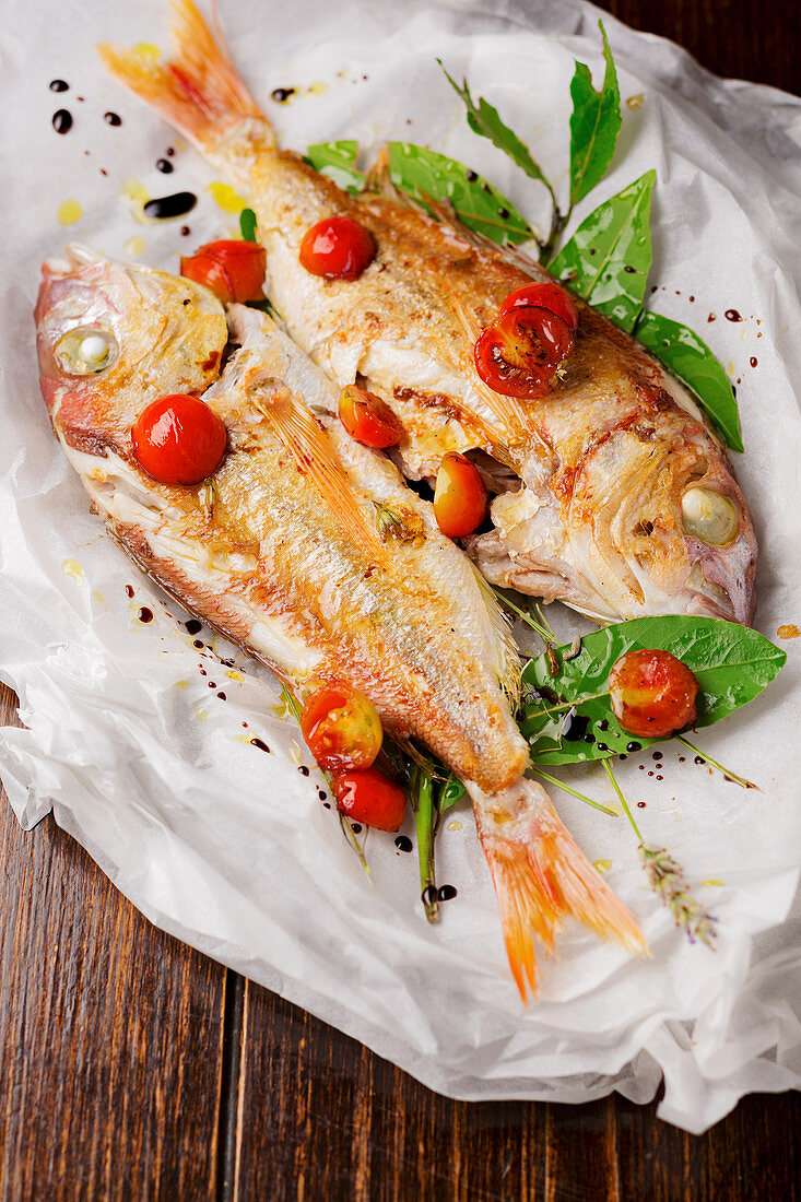 Oven roasted fish with cocktail tomatoes and laurel in parchment