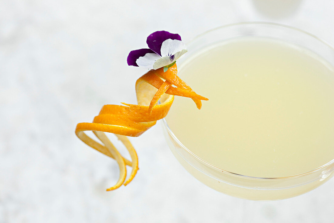 Elaborate orange garnish with a flower on the side of a cocktail