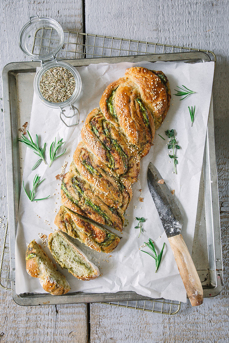 Savoury yeast bread with pesto and herbs on a baking sheet (top view)