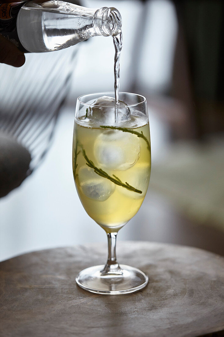 A samphire and tonic cocktail being poured