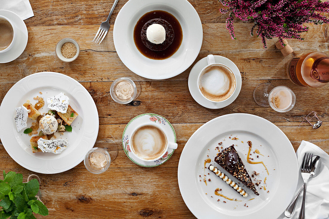 Selection of delicious desserts spread out on a table with coffee and champagne