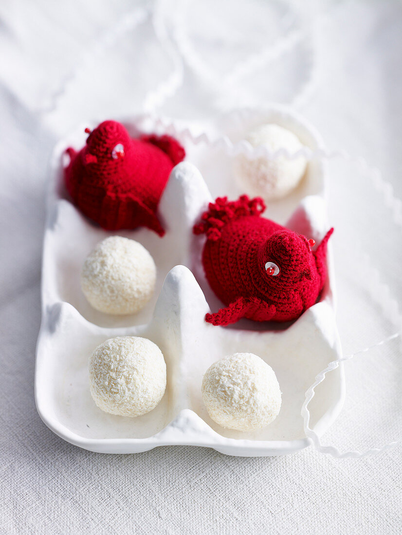 Crocheted red birds and truffle chocolates in a white egg box