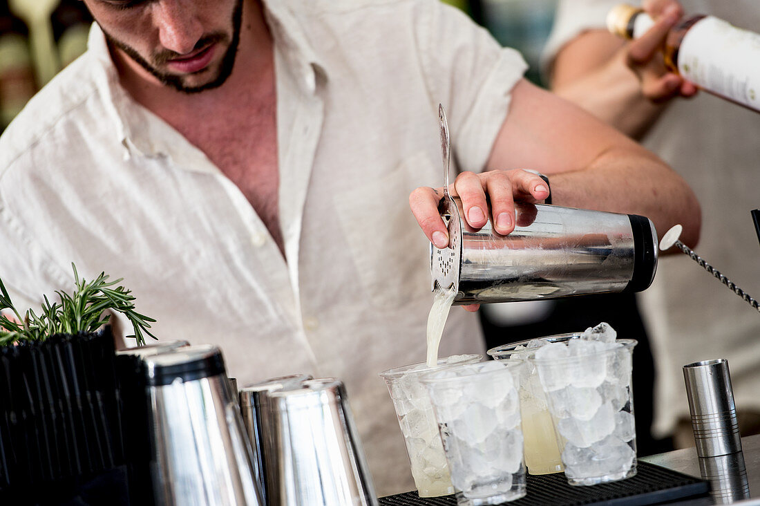 A bartender preparing cocktails with ice cubes