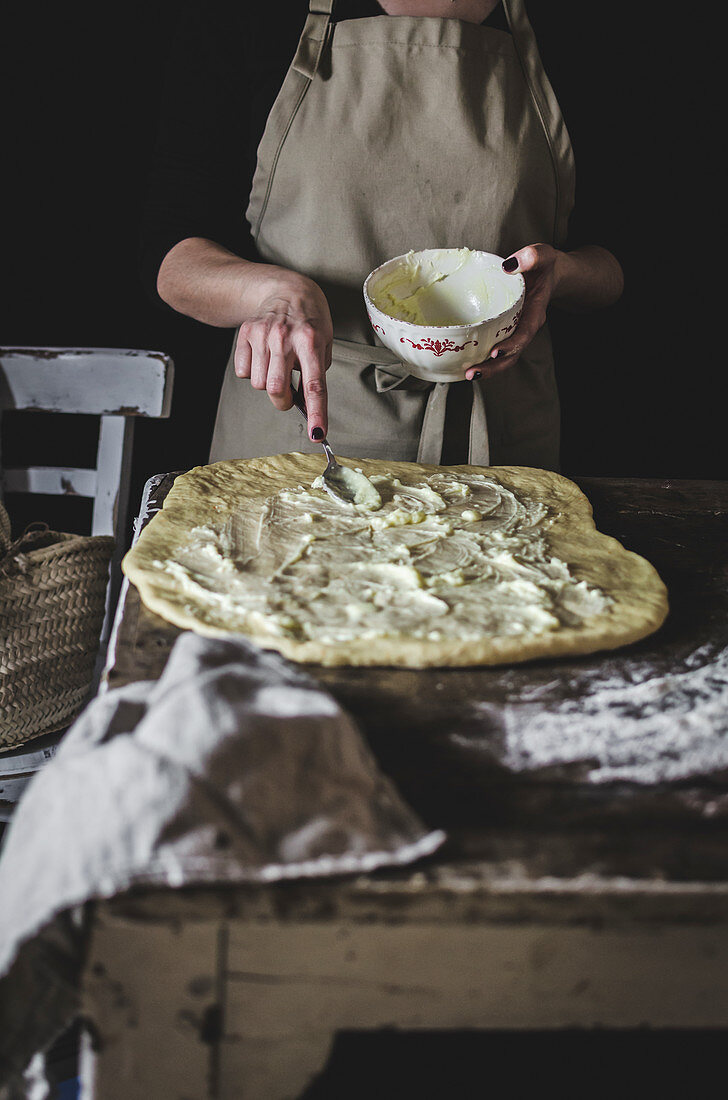 Woman putting stuffing on dough while cooking