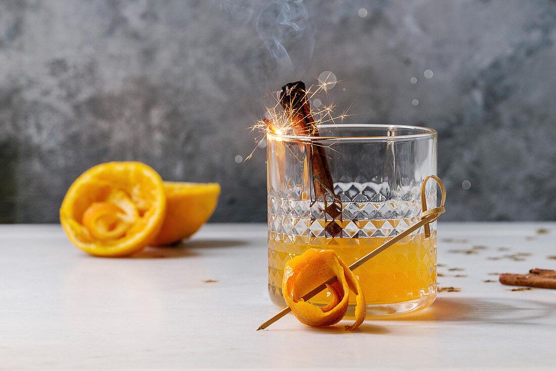 Glass of Scotch Whiskey orange juice alcohol cocktail with swirled orange peel and smoking cinnamon sticks