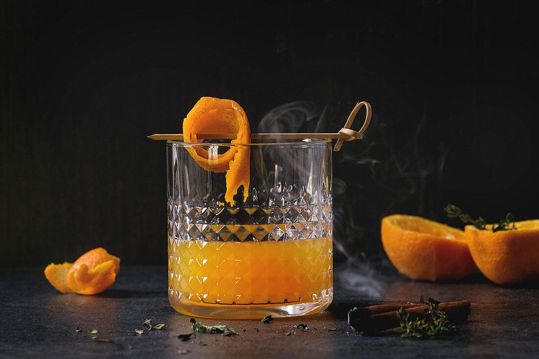 Glass of Scotch Whiskey orange juice alcohol cocktail with swirled orange peel on skewer, thyme and smoking cinnamon sticks
