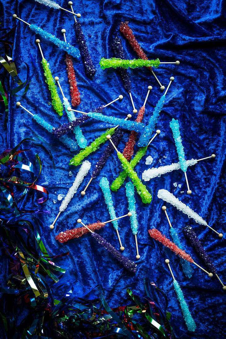 Very colorful assortment of rock candies on a blue velvet surface with sparkly streamers around