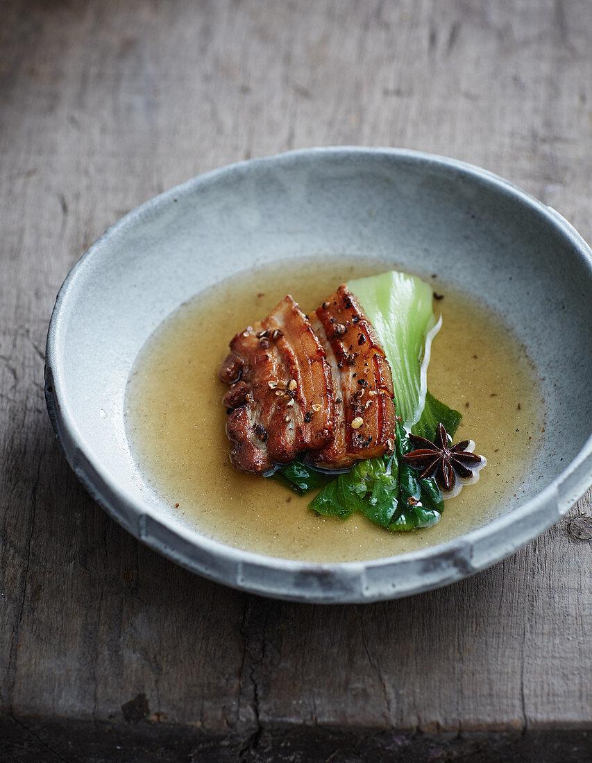Fried pork belly in a spicy oriental broth