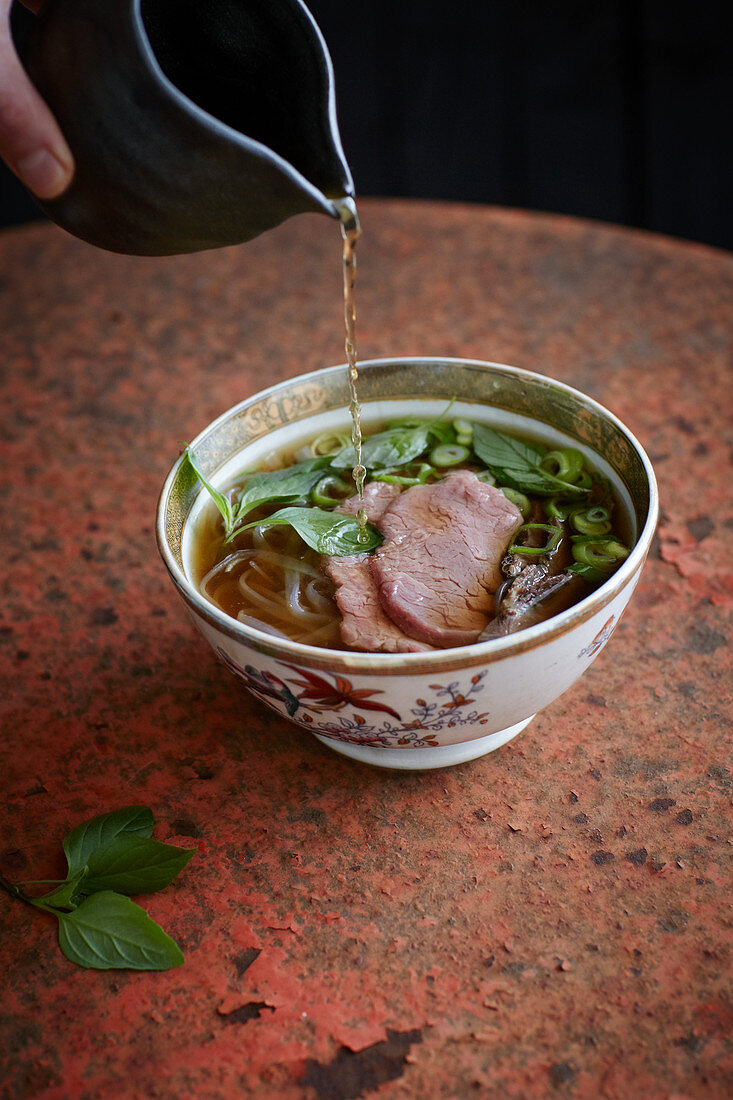 Beef broth being added to Vietnamese pho