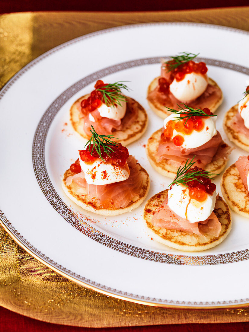 Blinis with creme fraiche smoked salmon and salmon caviar with red pepper and dill garnish