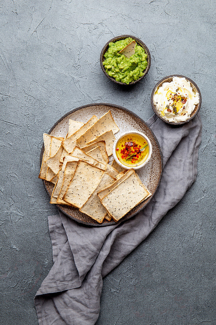 Bran chips, avocado guacamole, olive oil with spices, cream cheese