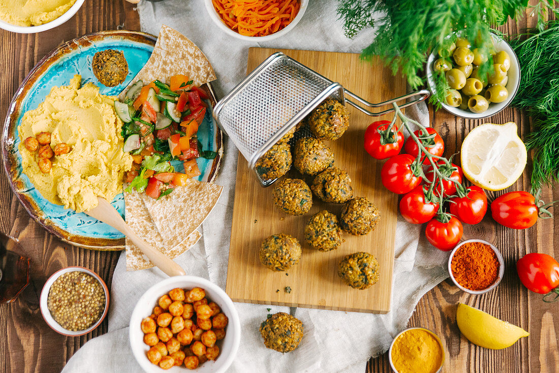 Fried falafel balls on wooden board surrounded with different ingredients