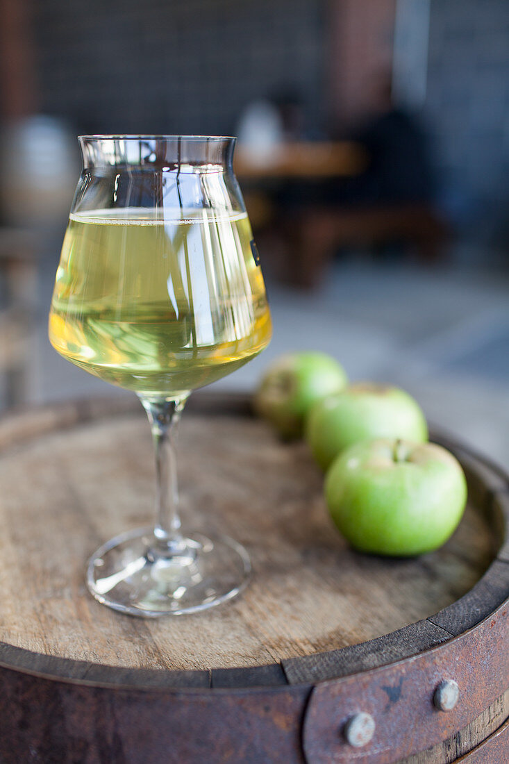 A glass of cider and green apples