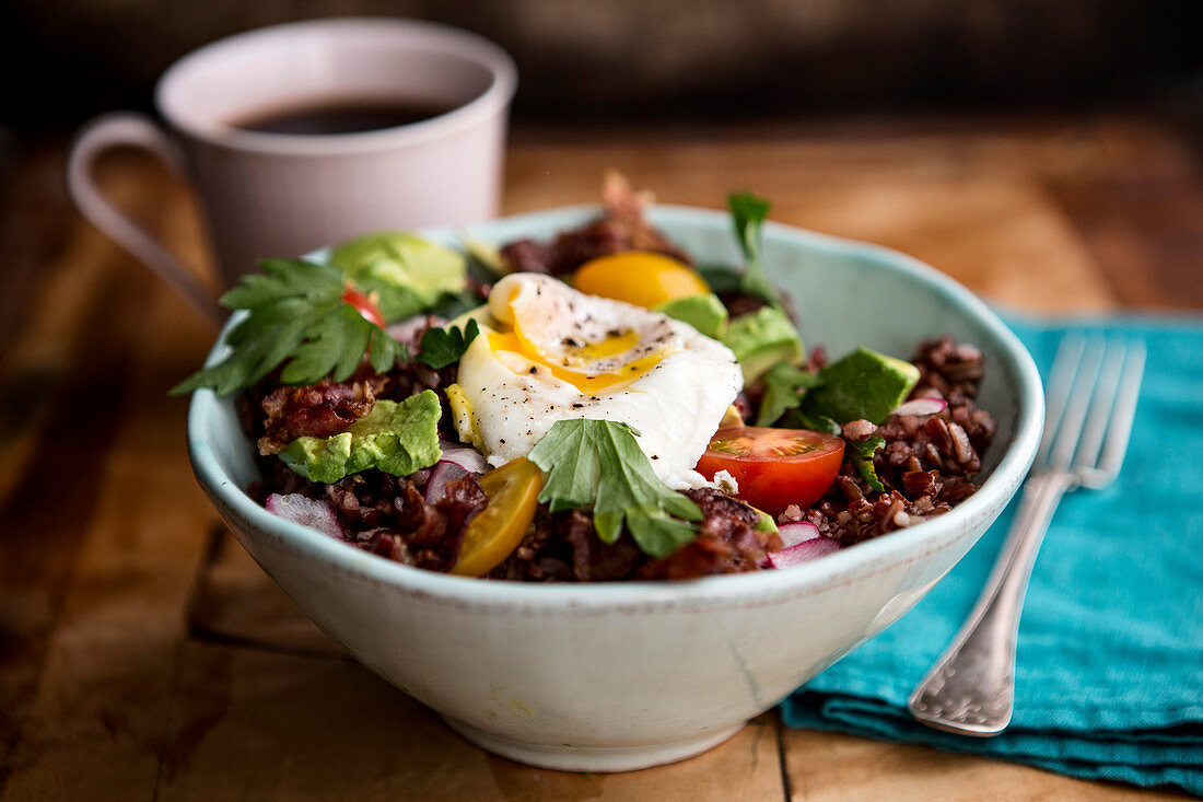 A rice bowl with poached eggs and bacon
