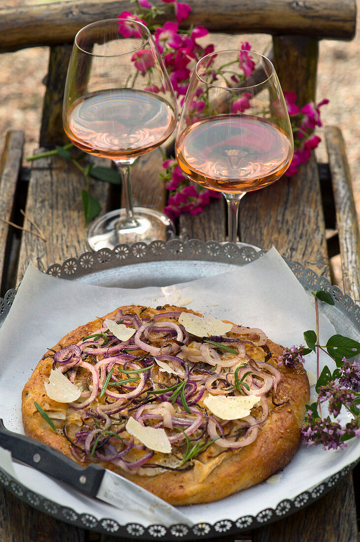 Focaccia with a trio of cheese, onions and rosemary on a table outside