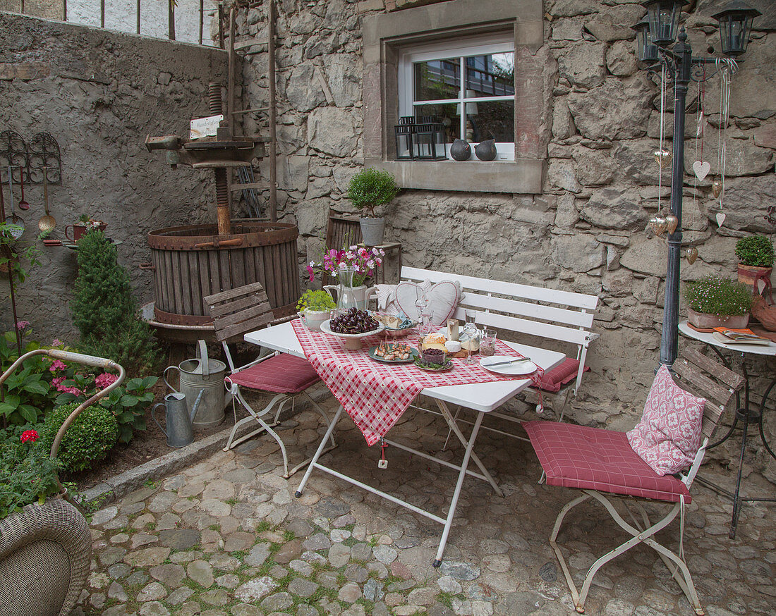 Set table with chairs and bench next to vintage wine press on cobbled terrace