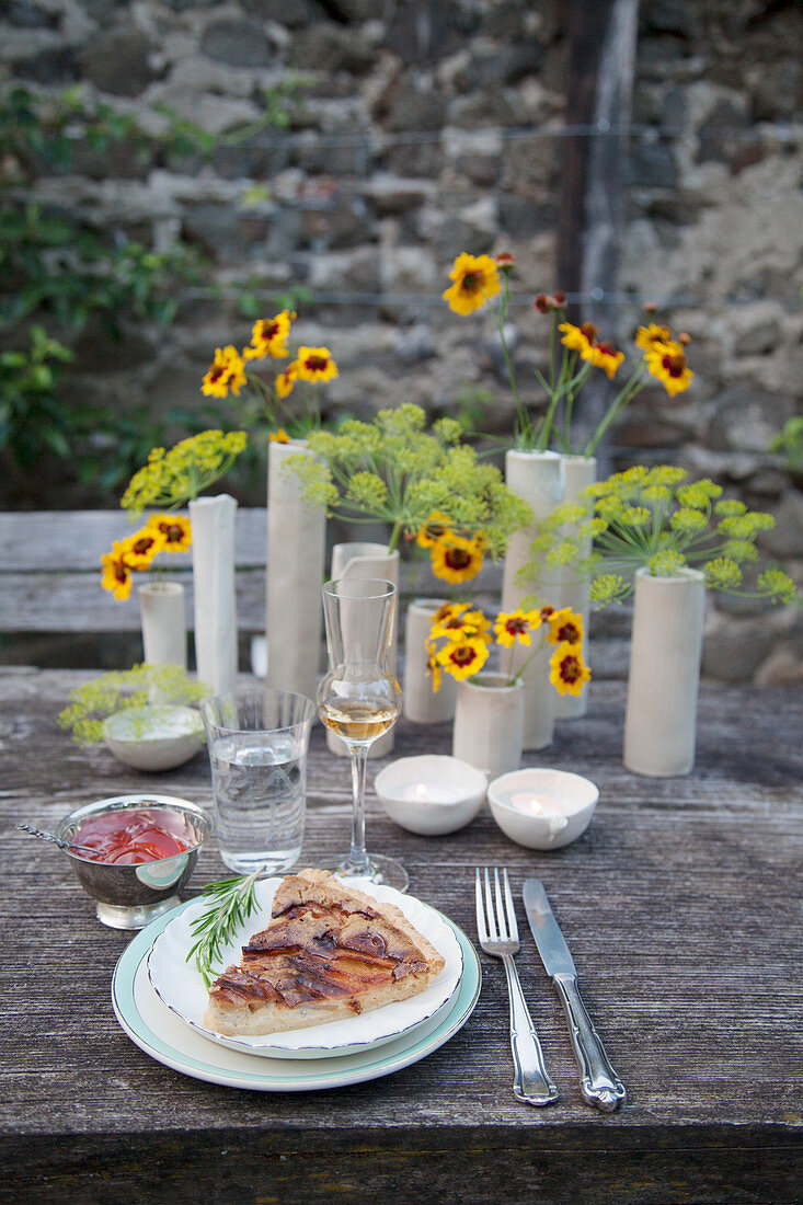 Piece of quiche and ceramic vases of flowers on garden table