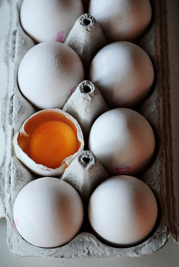 Eggs, whole and cracked, in an egg box