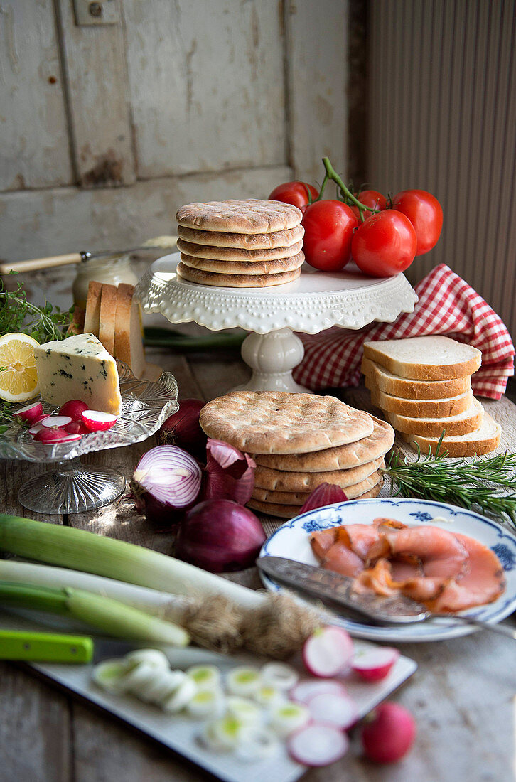 A buffet with ingredients for making Smorgastarta: flatbread, toast, smoked salmon, cheese and vegetables
