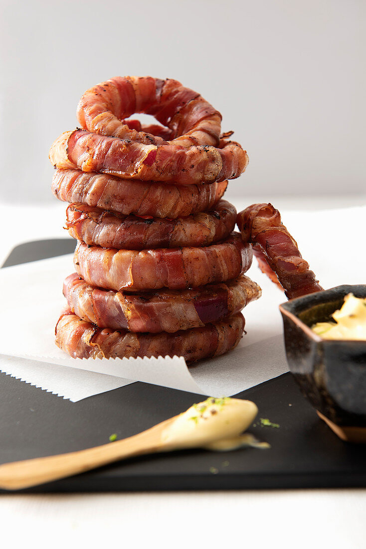 Onion rings wrapped in bacon with a lime mayonnaise