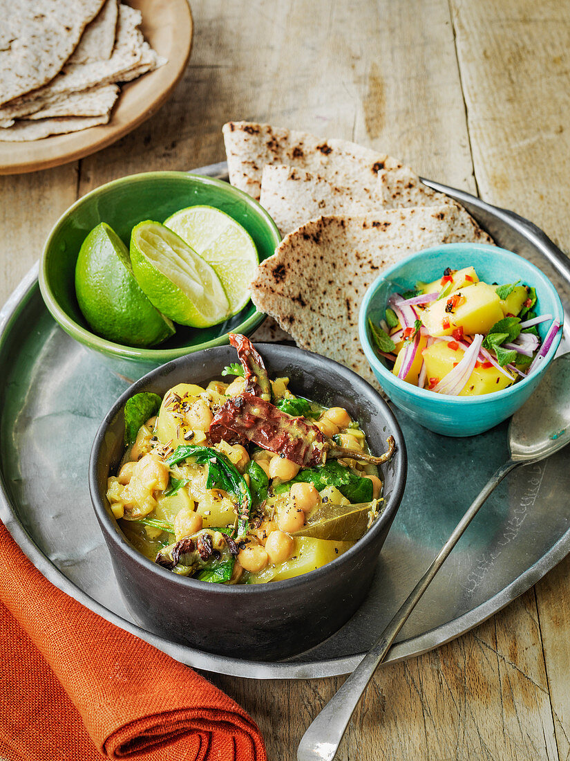 Slow cooked Indian vegan chic pea curry with potato salad and roti bread