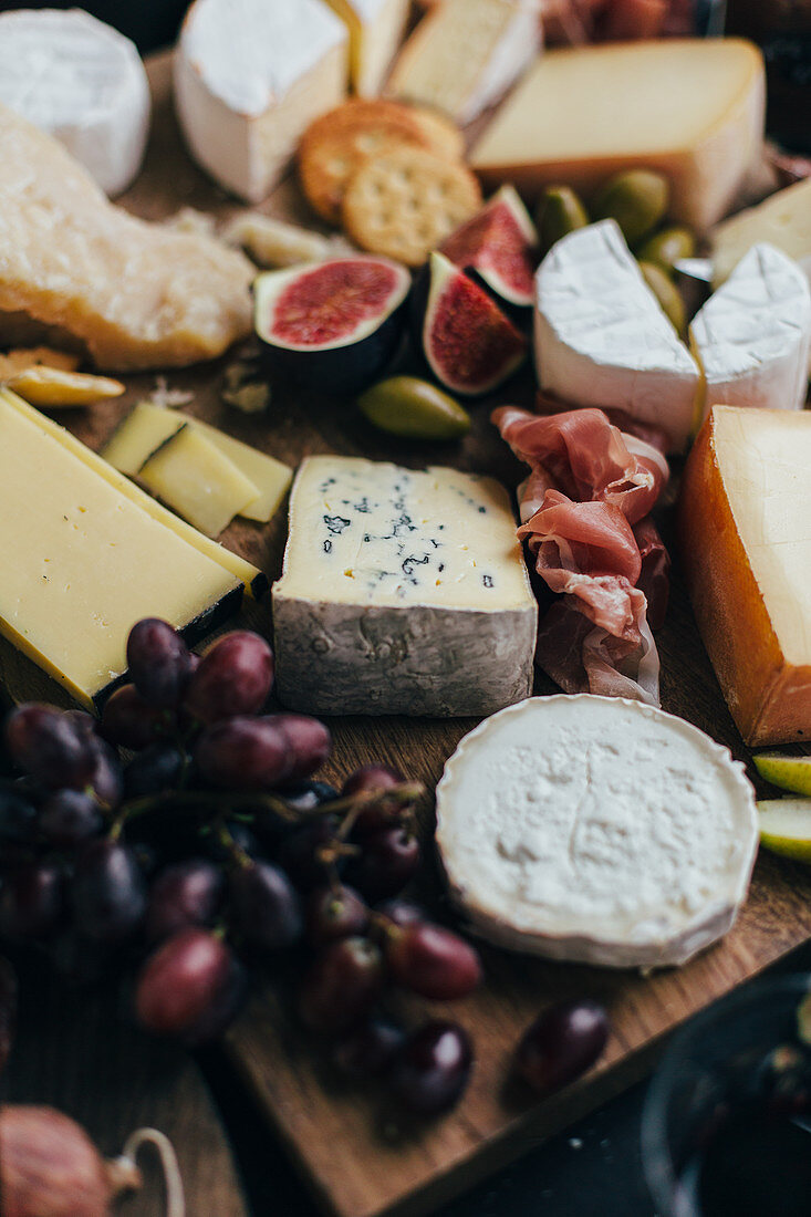 A cheese plate with figs, grapes, parma ham, olives and pears