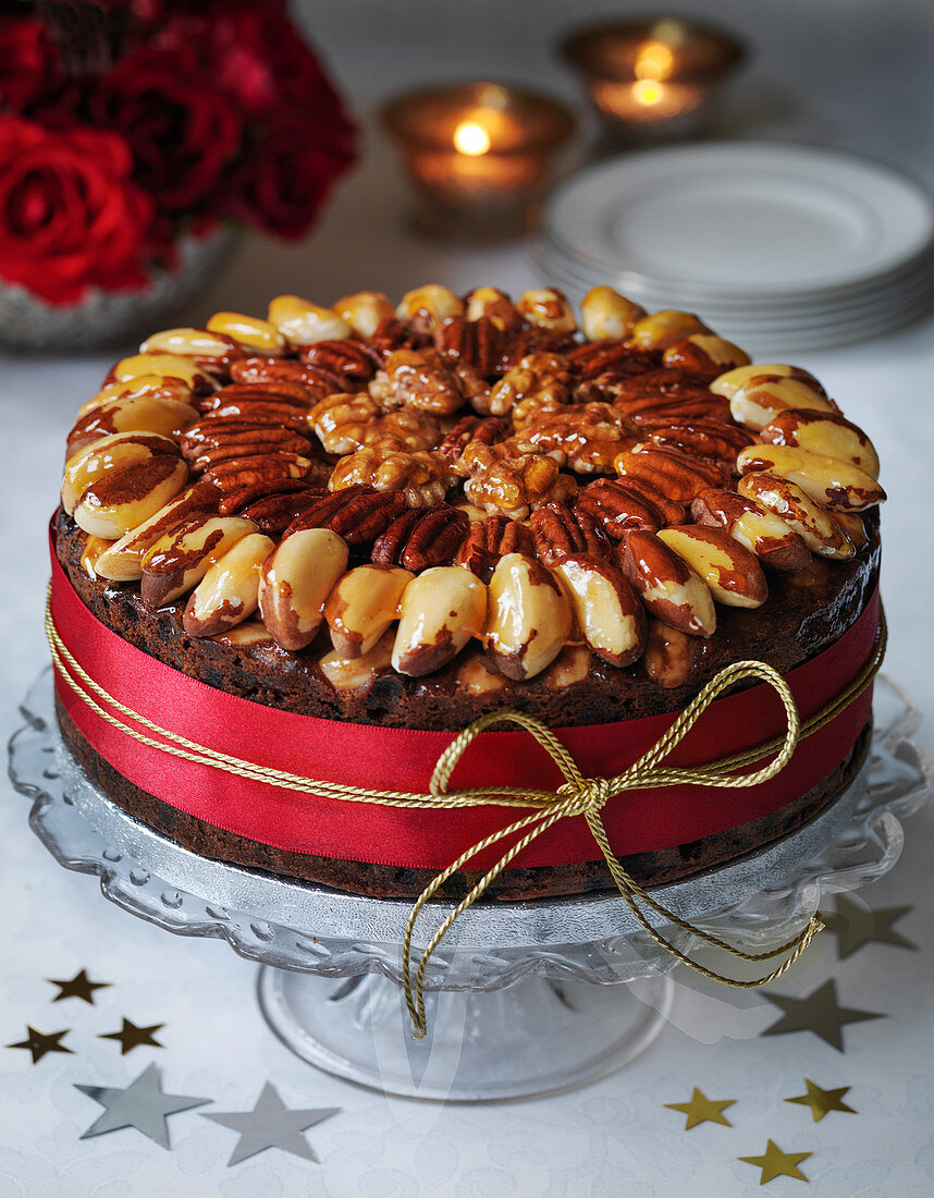 Classic Christmas cake with walnut brazil pecan nut glazed topping roses and candles