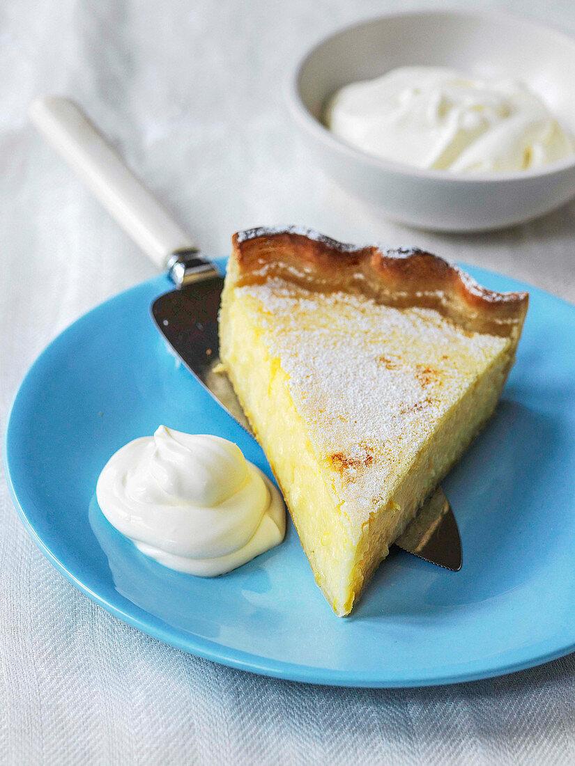 Slice of lemon tart with powder sugar and whipped cream