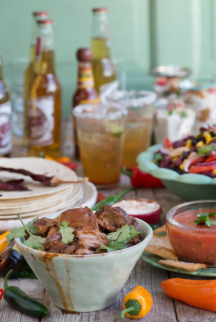 A Tex-Mex buffet with tortilla, spicy lamb, salsa, bean salad and guacamole (Mexico)
