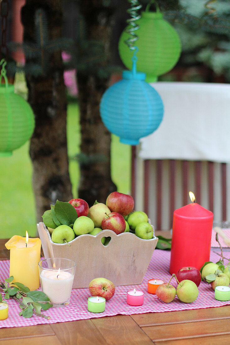 A table laid for a garden party with fresh apples and candles