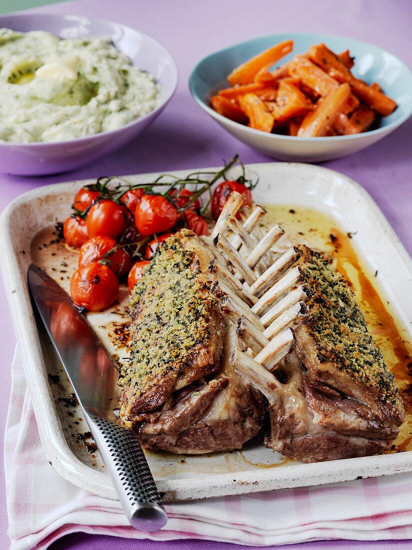 Roast rack of lamb with hetrb crust with roast tomatoes mash potato and glazed carrots