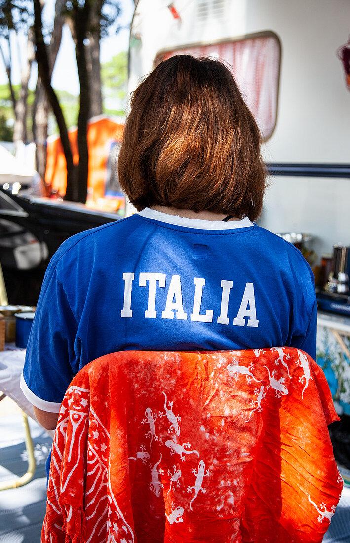 Frau sitzt im Schatten vor Wohnwagen (Italien)